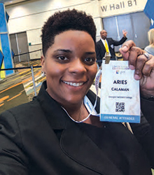 Aries Calaman '20 holding up her conference entry badge.