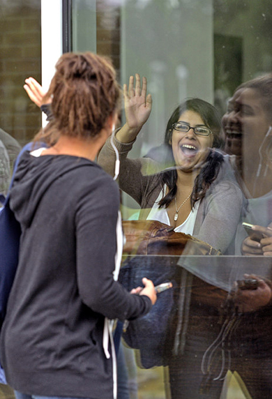 student waving to friend in campus coffee shop