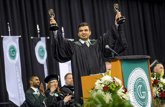 Homero Gonzalez holding up his Emmys during his commencement address.