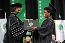 Dr. Jann L. Joseph handing diploma to Courtney Williams