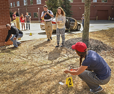 students examining mock crime scene, outside
