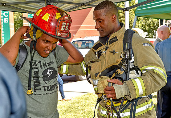 Student with firefighter trying on helmet