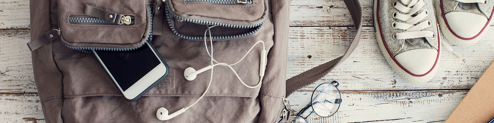 backpack, cell phone, earbuds and sneakers