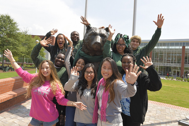 Waving GGC Students gathered around the iconic Grizzly statue.