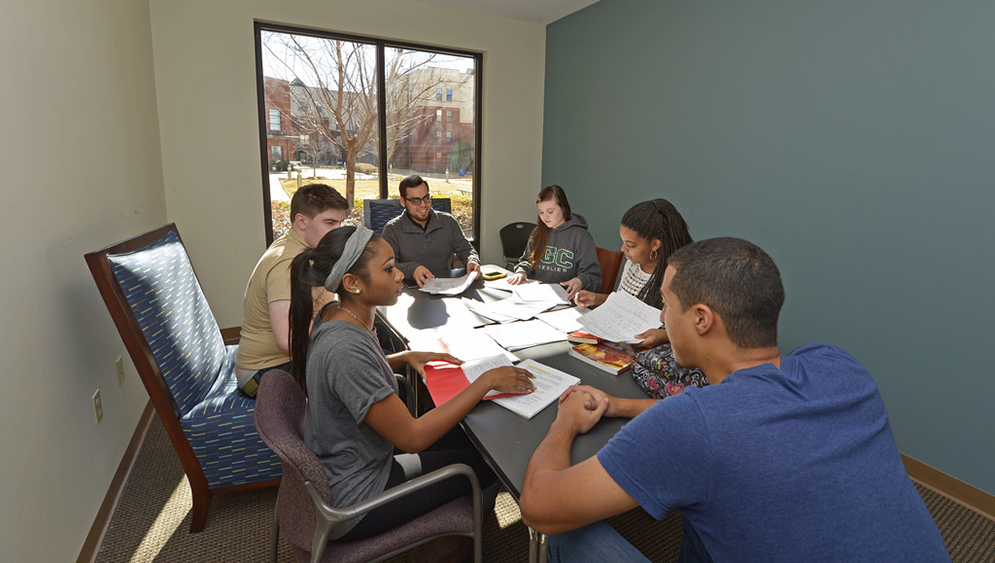 students collaborating in housing meeting room
