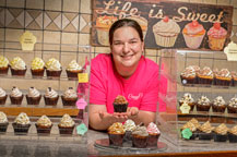 Andrea Ide surrounded by cupcakes
