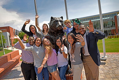 Welcoming students posing with Grizzly statue.