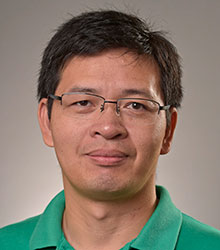 man wearing glasses and green shirt smiling at camera