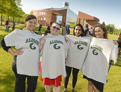 Four alumni displaying their new alumni t-shirts
