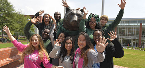 Students waving a greeting with Grizzly statue