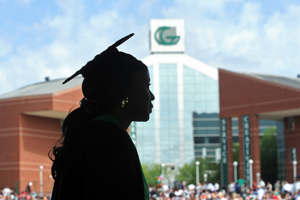 Graduate silhouetted in front of the signature Portman building.