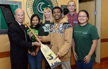 5 students present Dr. Kaufman with paddle