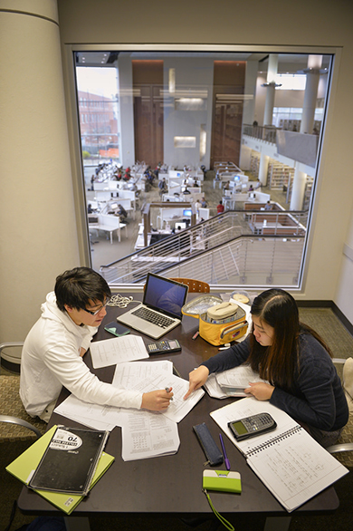 students completing homework in library study room